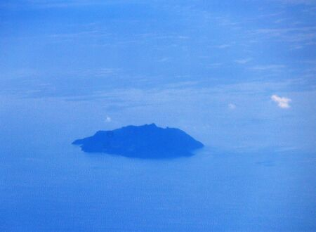 evocative image of an island that can be glimpsed between blue sky and blue sea Archivio Fotografico - 127175739
