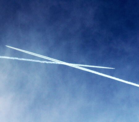 two trails of airplanes crossing in the sky 免版税图像