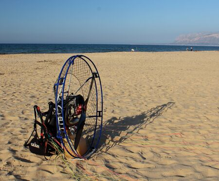 interesting image of petrol engine and propeller with protection for paragliding sail by the sea