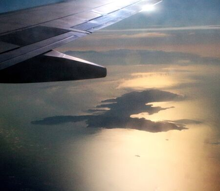 evocative image of the island of Elba seen from the porthole of an airplane with the wing in the foreground