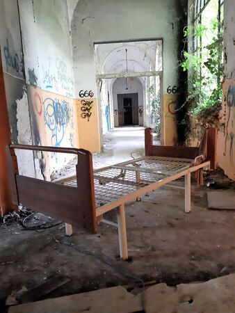 2019.09.28 - Limbiate, Milan, Italy, photographic reportage asylum in Mombello, abandoned psychiatric hospital bed base abandoned in a lane with writings on the walls and vegetation entering through the broken window
