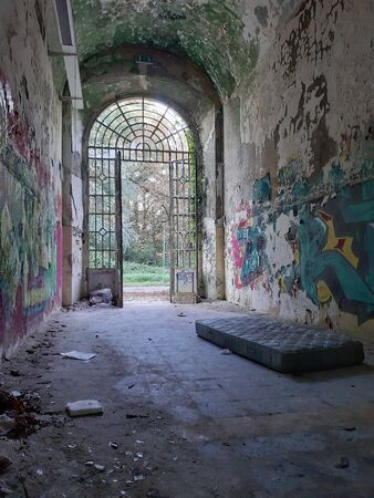 2019.09.28 - Limbiate, Milan, Italy, photographic reportage asylum in Mombello, abandoned psychiatric hospital abandoned mattress in the entrance of the structure, entrance with ruined walls and writings on the walls