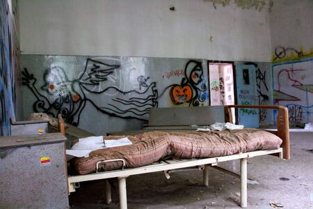 2019.09.28 - Limbiate, Milan, Italy, photo reportage asylum in Mombello, abandoned psychiatric hospital overturned hospital network with upturned cabinets in the background and written on the walls Stok Fotoğraf