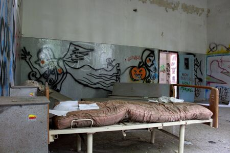 2019.09.28 - Limbiate, Milan, Italy, photo reportage asylum in Mombello, abandoned psychiatric hospital hospital bed with upturned cabinets in the background and writing on the walls