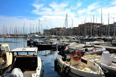 evocative image of sailboats moored in the harbor on a sunny day