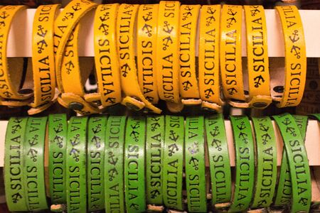 """yellow and green leather bracelets with the word """"Sicily"""" and two anchors printed to promote the Sicily region in Italy"""