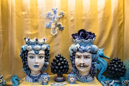Dark brown heads and pinecones of blue ceramic of handmade production Sicilian to promote the Sicily region in Italy