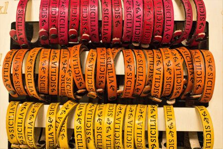 """red, orange and yellow leather bracelets with the word """"Sicily"""" and two anchors printed to promote the Sicily region in Italy"""