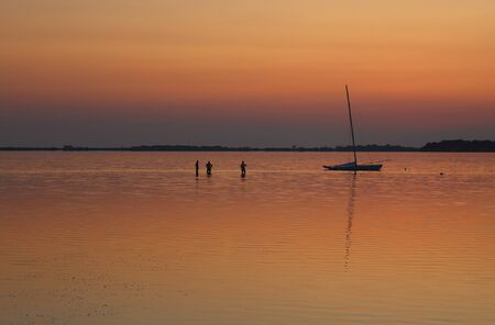 sailing boat moored on the sea at sunset and headland on the background