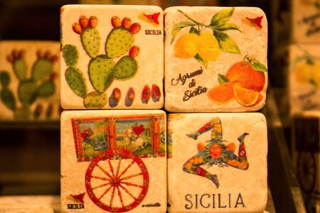 colored images reproduced on cube-shaped stones promoting the Sicily region in Italy depicting citrus fruits, lemons, oranges, cactuses typical Sicilian cart and female head with three folded legs called
