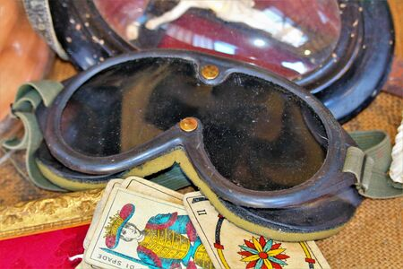 Milan, Italy, 2017.05.21 evocative image of old biker / aviator glasses on top of old playing cards at a vintage market