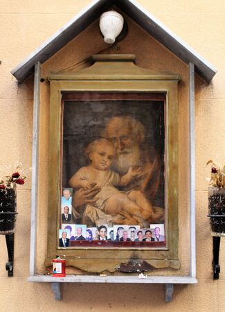 evocative image of a votive chapel dedicated to a saint hanging on a wall in the historic center of Palermo in Italy