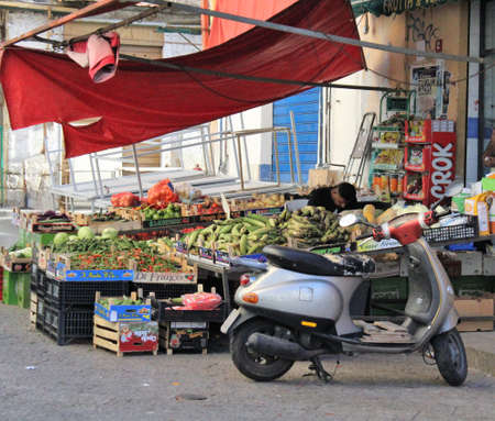 evocative image of a fruit and vegetable shop with fruit and vegetables displayed for sale and a scooter in the foreground in the historic center of Palermo in Italy