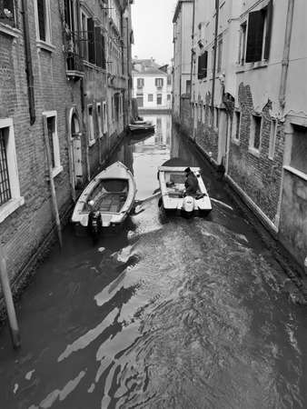 Venice, Italy, January 27, 2020 evocative black and white image of motorboats moving along a calle
