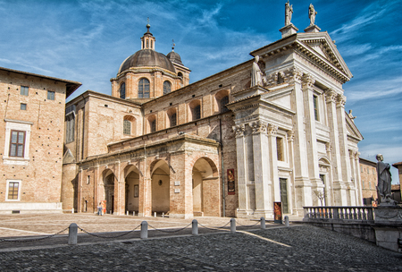 Urbino, Italy - April 10, 2017: tourists in front of Cathedral in Urbino Italy. The historic center of Urbino is a UNESCO World Heritage site and Represents the zenith of Renaissance architecture