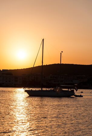 Sailboat at sunset, silhouette in backlight, yacht golfo aranci sardinia 写真素材