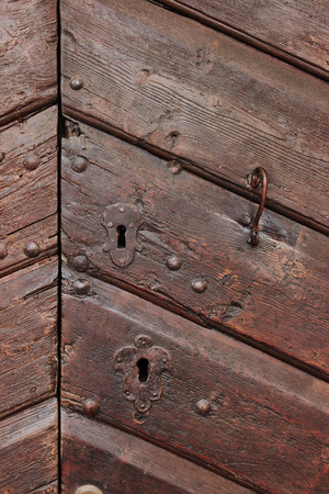 Detail of an old wooden doorway with metal lock and handle photo