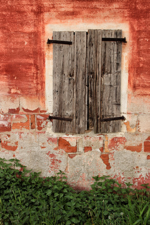 naif: An old wood window on a red peeling wall and wild grass Stock Photo