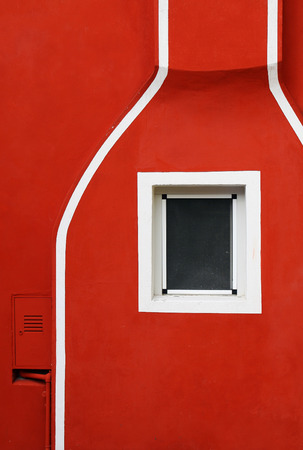 Detail of a red facade with white lines and a small window  photo