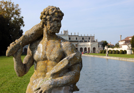 eroded: Statue by the pool in the huge park of Villa Pisani, Italy Editorial