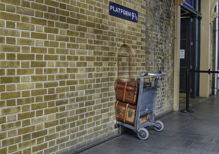 London, United Kingdom, June 2018. Platform 9 and 34 at Kings Cross Station, London. A trolly stuck in the wall where fans emulate the Harry Potter adventures. A service assistant for the photo.