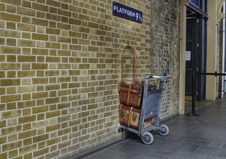 Londres, Reino Unido, junio de 2018. Andén 9 y 3/4 en Kings Cross Station, Londres. Un carrito pegado en la pared donde los fanáticos emulan las aventuras de Harry Potter. Un asistente de servicio para la foto. Editorial