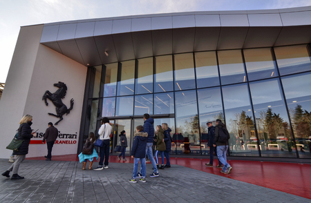 Maranello, Italy, December 2018. Entrance to the Ferrari museum, The black prancing horse leaves no doubt: we are in the home of engines. People stop for a souvenir photo.