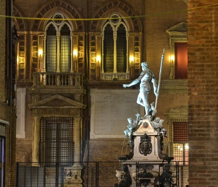 Bologna, Emilia Romagna, Italy. December 2018. The Neptune fountain at night, for New Year's Eve, is illuminated with colored lights and has been fenced to protect it.
