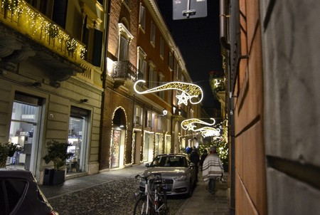 Modena, Emilia Romagna, Italy. December 2018. Night view of the streets of the historic center. The Christmas atmosphere is underlined by the bright decorations. People stroll enjoying the place.