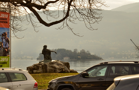 Verbania, Piedmont, Italy. March 2019. Suggestive image of the lake with a statue facing the water towards the island and a tree that frames it. 新聞圖片