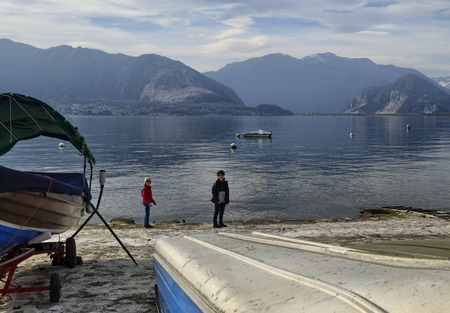 Verbania, Piedmont, Italy. March 2019. The lakefront offers a view of an idyllic landscape. Moored boats, small islands with luxuriant nature. Tourists stroll along the streetlights.