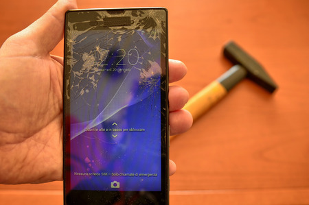 Close up on a smartphone screen with a broken screen and a thousand cracks. A hammer in the background. The display has been turned on to test its operation.