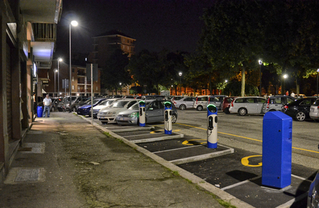 Turin, Italy, Piedmont 9 June 2018. Night view of an electric car rental station, parking with fast charging points. Blue Turin Society.