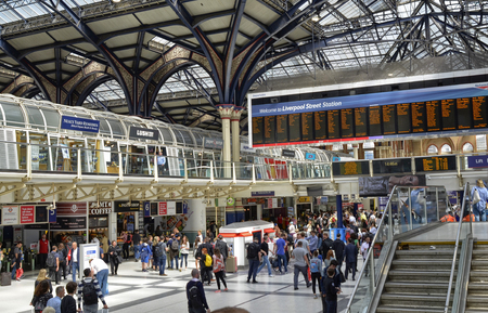Liverpool street station, London United Kingdom, 14 June 2018. The main hall of the station, buzzing with people, the informative luminous display boards, automatic terminals and the glass canopy. Редакционное