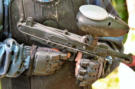 Paintball battle. Detail of the rifle held by a player: you can see the hands with protective gloves and the tank of paint bullets on the top of the rifle. Stock Photo