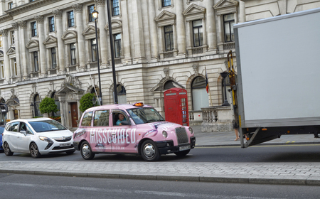 London, United Kingdom, June 2018. London taxis, called cabs. Traditionally of strictly black color, today they are seen with extravagant advertising colors. This case a nice rose!