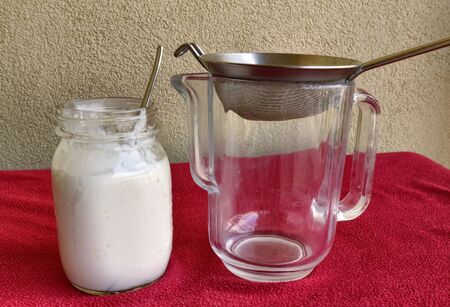 Pouring of Kefir, the glass jar is placed next to the net to pour the contents.