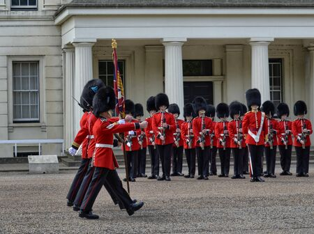 London, UK, June 2018. In the Wellington Barracks courtyard, royal guards prepare for the ceremonial of changing of the guard. A small group of guards walks in front of the platoon