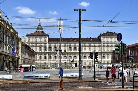 Turin, Piedmont, Italy. June 2019. View of the royal palace from via Pietro Micca: the palace acts as a majestic backdrop to the square. Blue summer sky with white clouds.