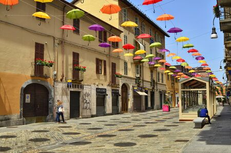 Turin, Piedmont, Italy. June 2019. Installation born with the street artists festival. Colored umbrellas, hanging between the houses along the alleys, give shade and joy with their bright colors.