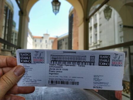 Turin, Piemonte, Italy. June 2019. The entrance ticket to the Teatro Regio in Turin, with the background of the inner courtyard of the theater blurred. Editorial