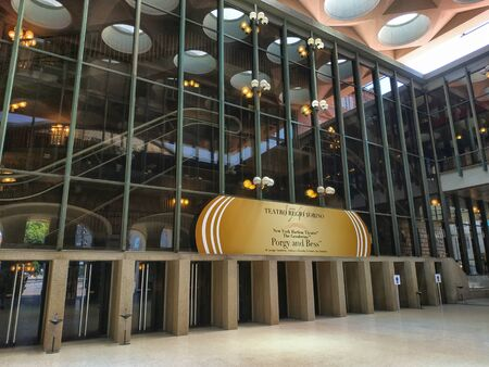 Turin, Piemonte, Italy. June 2019. The modern entrance of the Teatro Regio di Torino. A large golden sign shows the title of the work being programmed.