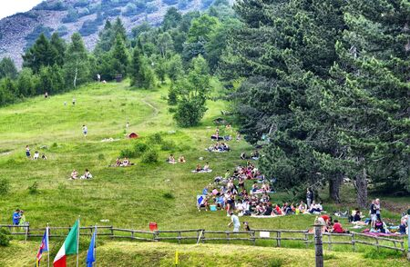 Colle del Lys, Piedmont, Italy. July 2019. People looking for refreshment take advantage of the slope of the mountain with a large green lawn to picnic. The passage of clouds is recognizable.