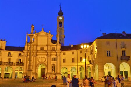 Venaria Reale, Piedmont, Italy. July 2019. Piazza della Annunziata is the historic heart of Venaria Reale, people crowd the restaurants of the square dominated by the bell tower of the church Editorial