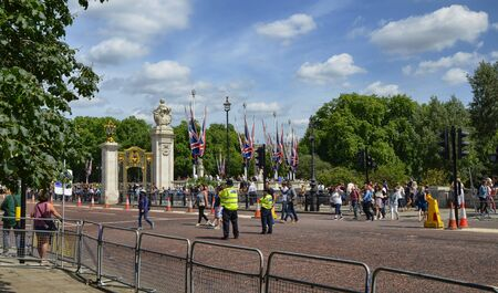 London, United Kingdom, June 2018. The ceremonial change of the guard leaves Birdcage Walk. People are crowded at the entrance to Buckingham Palace, awaiting the arrival of the gurdies.