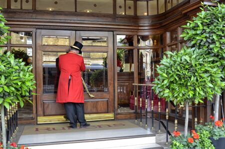 London, United Kingdom, June 2018. The typical uniform of the porters of London hotels, in this photo the Rubens hotel of red color.