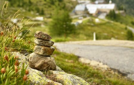 Stones stacked as a Zen memorial along a mountain road, a township in the background blurred and indistinguishable.