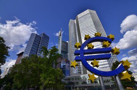 Frankfurt am Main, Germania, agosto 2019. L'Eurotower. Nuvole bianche sul cielo azzurro. Evidenziato a destra è il simbolo dell'euro blu con stelle gialle. Editoriali
