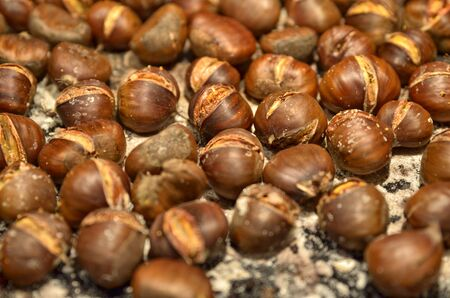 A metal baking pan filled with chestnuts roasted as far as the eye can see. Selective focus on chestnuts in the center. Note the salt crystals with which the pan was sprinkled.