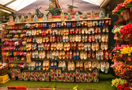 Amsterdam, Holland, August 2019. At the flower market in vast display of Dutch clogs. Classic souvenirs for tourists, represented here with a multitude of colors. Below the word flower market Stock fotó - 139049858
